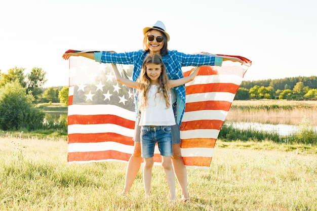 Positive portrait of mom and daughter with american flag