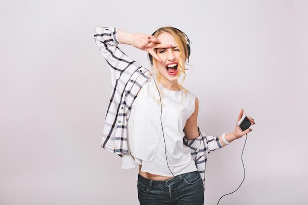 大きなヘッドフォンで音楽を聴くカジュアルな服装でブロンドの髪を持つうれしそうなエネルギー少女の肯定的な肖像画。彼女は踊っていて、スマートフォンを持っています。分離されました。