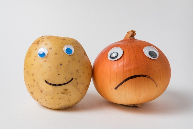 Positive potato and a sad napiform onion with googly eyes on white background. pessimist and optimist concept