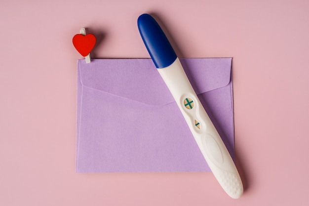 A positive pregnancy test in an envelope pregnancy message concept good news