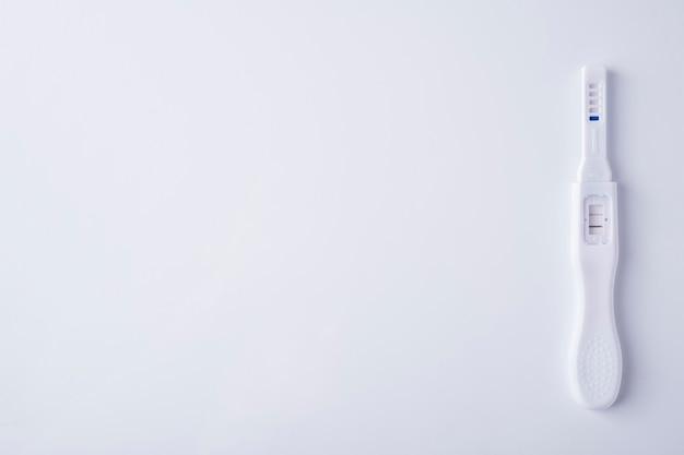 白い背景の陽性妊娠検査。上面図、