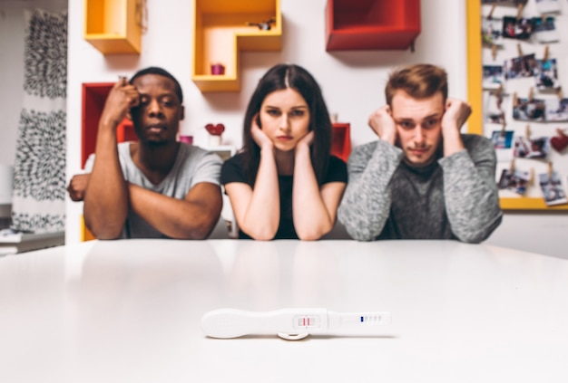Positive pregnancy test, one woman and two man, three people, polygamy