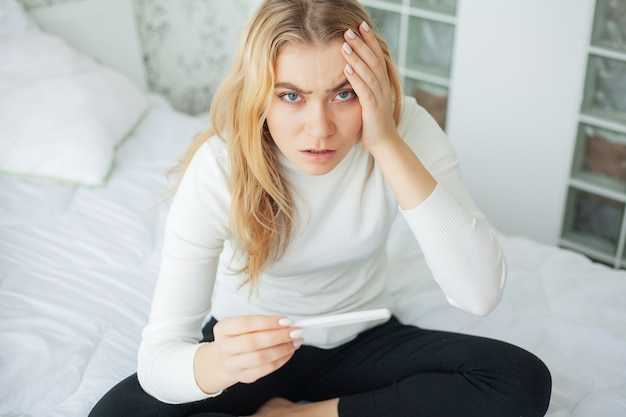 Positive pregnancy test, young woman feeling depressed and sad after looking at pregnancy test result at home