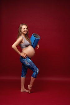 Positive pregnant woman in sports clothes holds a gym mat in her hands.