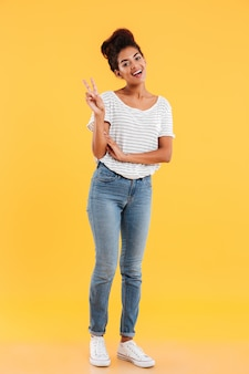 Positive pretty african woman standing isolated and showing peace gesture isolated