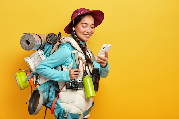 Positive pretty asian tourist uses modern gadget for navigating, dressed in hat and jumper with jacket, uses binoculars, retro camera, karemat during trip stands against yellow wall