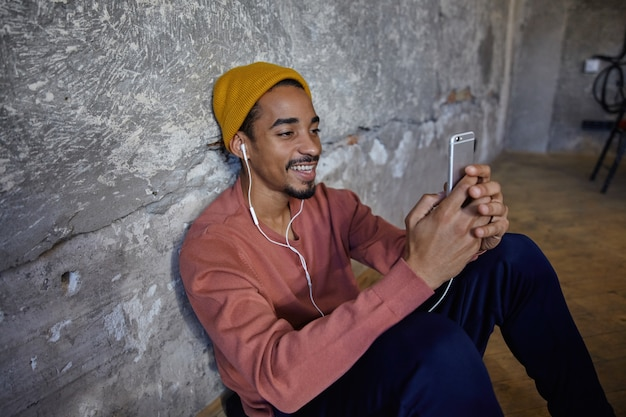 Positive pretty bearded dark skinned guy leaning on concrete wall while sitting on floor, wearing earphones and holding smartphone in raised hands, smiling while looking on screen