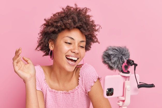 Positive pretty brunette afro american female blogger focused at smartphone on tripod makes online streaming has own channel smiles gladfully poses against pink wall. vlogging concept.