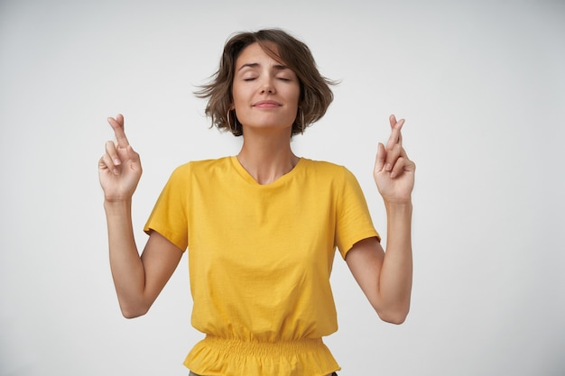Positive pretty brunette female with casual hairstyle standing with closed eyes, crossing her forefingers for good luck, making wishing gesture