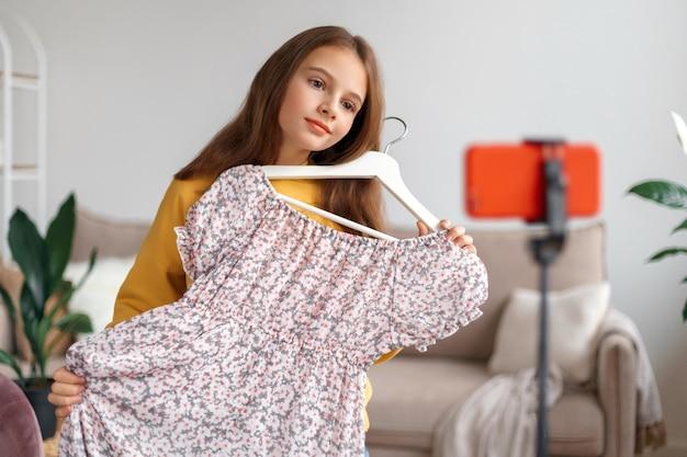 Позитивная симпатичная девушка держит новое платье и делает замечания о его качестве и цене, записывая видеоблог для своих подписчиков на камеру смартфона