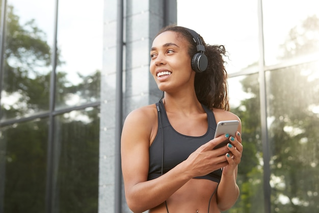 Donna dalla pelle scura abbastanza sana positiva con l'acconciatura a coda di cavallo tenendo lo smartphone in mano e guardando da parte con un sorriso felice, in posa sull'ambiente urbano in cuffie e vestiti sportivi neri