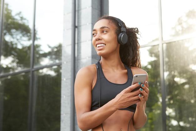 スマートフォンを手に保ち、幸せな笑顔で脇を見て、ヘッドフォンと黒いスポーティな服で都会の環境でポーズをとるポニーテールの髪型を持つポジティブなかなり健康的な暗い肌の女性