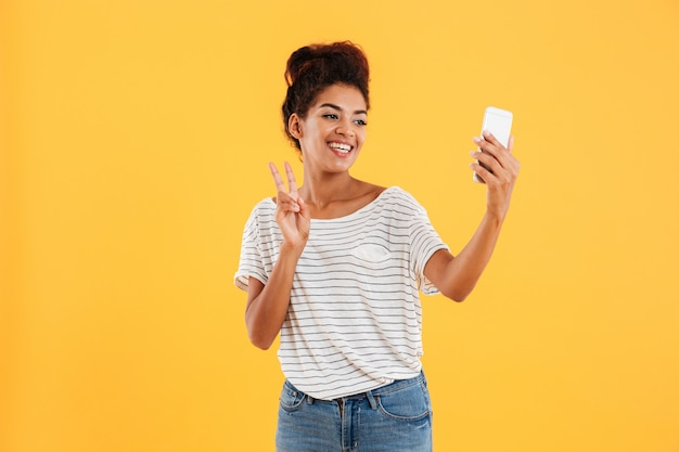 Positive pretty lady making selfie on phone isolated
