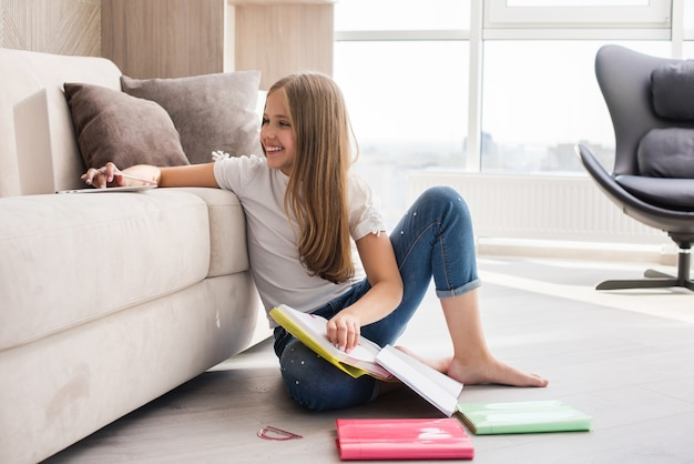 Positive pretty preteen female schooler make homework with paper colorful notepads and pencil at home interior in jeans barefoot
