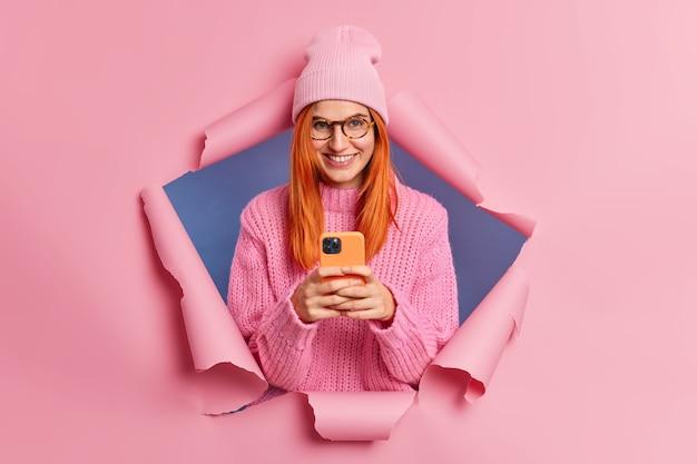 긍정적 인 예쁜 빨간 머리 소녀는 문자 메시지에 휴대 전화를 사용하여 소셜 네트워크를 서핑하며 세련된 분홍색 모자와 스웨터를 즐겁게 착용합니다.