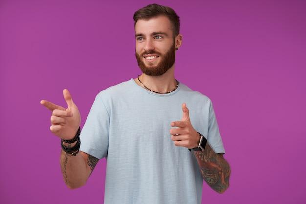 青いtシャツを着て、人差し指で脇を向いて、広く笑って、紫色でポーズをとって、流行のヘアカットを持つポジティブなかわいい入れ墨のブルネットの男