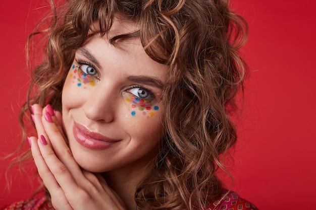 Позитивная симпатичная молодая женщина с романтической прической и разноцветными точками на лице смотрит с нежной улыбкой и опирается подбородком на сложенные руки, стоя