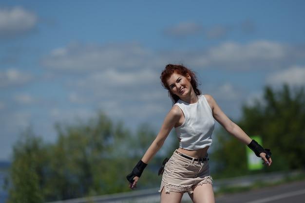 ローラースケートのショートパンツとトップスのスケートでポジティブなかなり若い女の子。