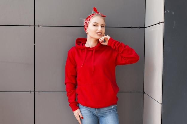 청바지에 세련된 두건이있는 트렌디 한 빨간 후드 티 셔츠에 긍정적 인 예쁜 젊은 여자가 서 있고 회색 건물 근처의 도시에서 웃고 있습니다.