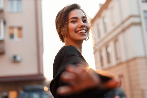 카메라에 그녀의 손에 도달 미소로 세련된 헤어 스타일로 긍정적 인 예쁜 젊은 여자