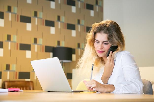 전화로 고객과 프로젝트를 논의하는 긍정적 인 전문가
