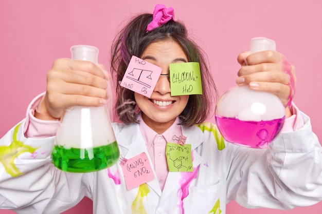 Positive professional female chemist holds two glass beakers has two stickers on eyes with written chemical formulas conducts scientific experiment dressed in uniform on pink
