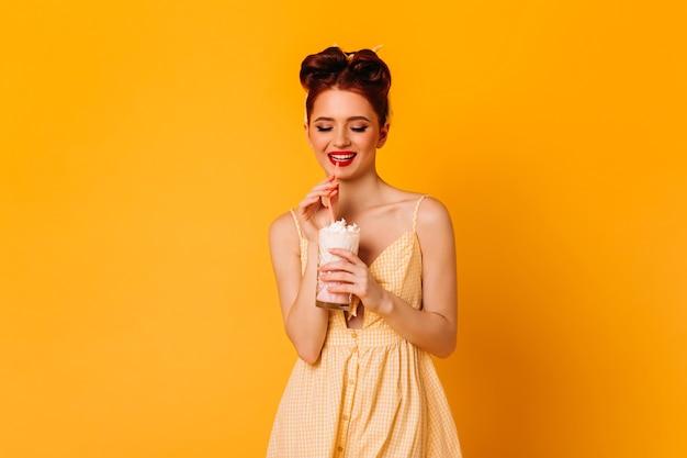 Ragazza dai capelli rossi positiva che beve milkshake. studio shot di blithesome pinup lady isolato su spazio giallo.