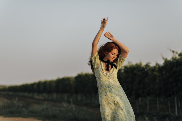 Positive red haired lady with black bandage on neck in green summer clothes smiling and posing with hands up on vineyards