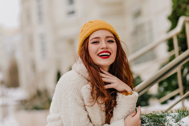 Positive red-haired woman laughing on blur nature. refined ginger girl smiling during winter photoshoot.