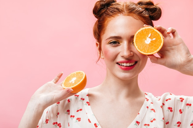 Positive red-haired woman in white dress eats juicy orange on pink background.
