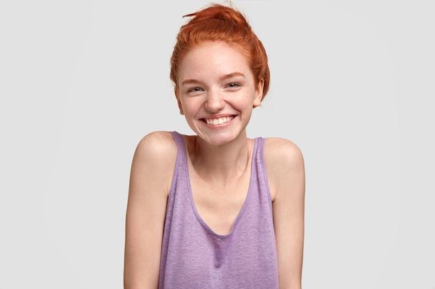 Positiva giovane donna dai capelli rossi con la pelle lentigginosa, si sente felice e fresca dopo i trattamenti di bellezza, sorride ampiamente, mostra i denti perfetti, modelli contro il muro bianco, esprime felicità