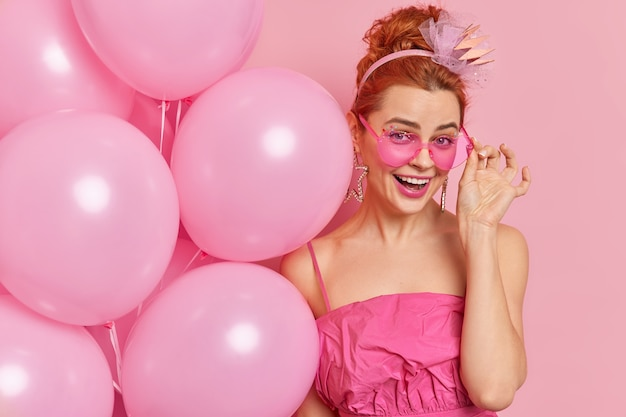 Positive redhead european girl smiles positively keeps hand on rosy sunglasses dressed in festive dress holds inflated balloons enjoys being on party celebrates graduation isolated on pink wall