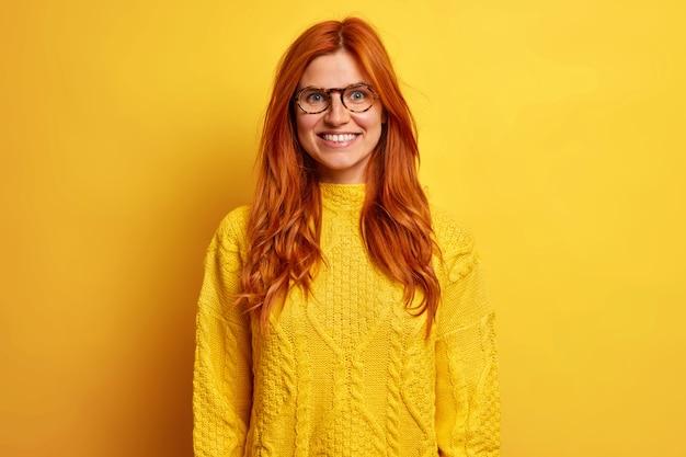 기쁜 얼굴 표정 미소를 지닌 긍정적 인 빨간 머리 유럽 여성은 성공적인 하루가 따뜻한 노란색 스웨터를 입은 후 기분 좋게 행복하다고 느낍니다.