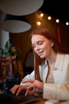 카페에서 마케팅 프로젝트에 참여하는 긍정적인 빨간 머리 여성 디자이너, 웃고