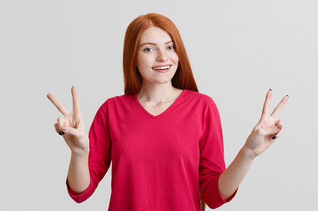 La femmina rossa positiva si diverte al chiuso, gesti e mostra il segno giusto, indossa abbigliamento casual rosso, isolato su un muro bianco. la donna graziosa con lo sguardo positivo esprime la sua approvazione e felicità