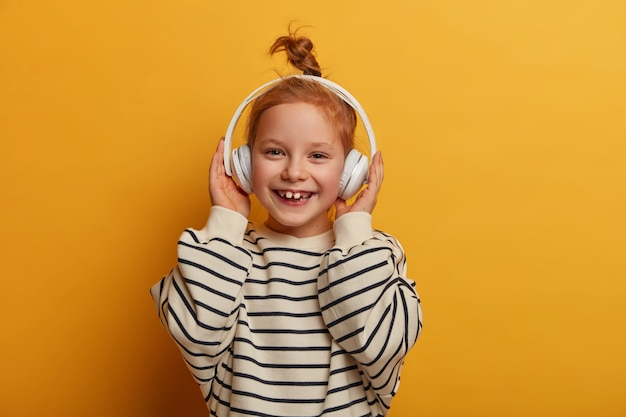 Positive redhead girl enjoys favorite tune, listens music in headphones, has optimistic mood, hair knot, wears striped jumper in casual style, poses against yellow wall, smiles toothily