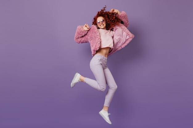 Позитивная рыжая девушка в эко-пальто, розовом топе и белых штанах прыгает на сиреневом пространстве.