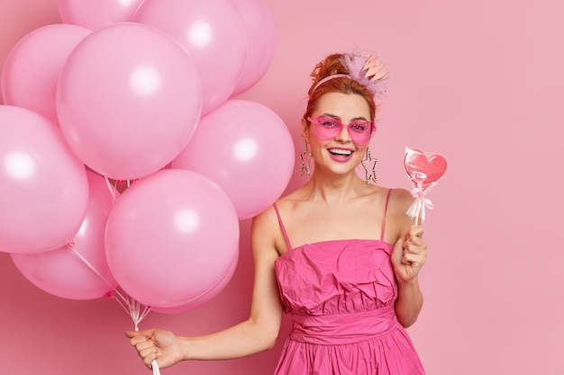 Positive redhead girl in trendy pink shades and dress holds tasty sweet candy and bunch of balloons has festive mood on party poses against rosy background.