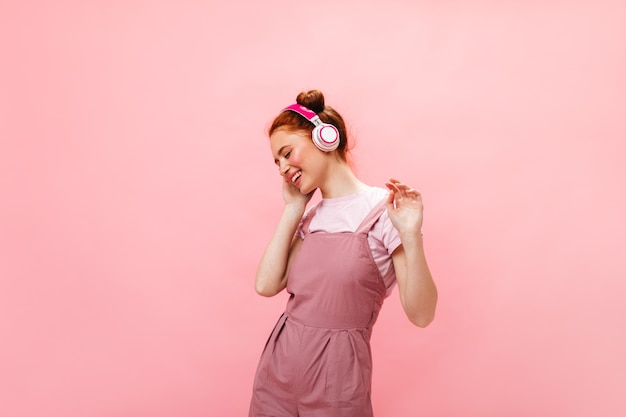 Positive redhead lady in pink outfit laughs while listening to music with pink headphones on isolated background.