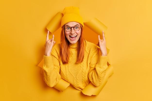ポジティブな赤毛の10代のヨーロッパの女性は角のジェスチャーを上げて手を笑顔にします