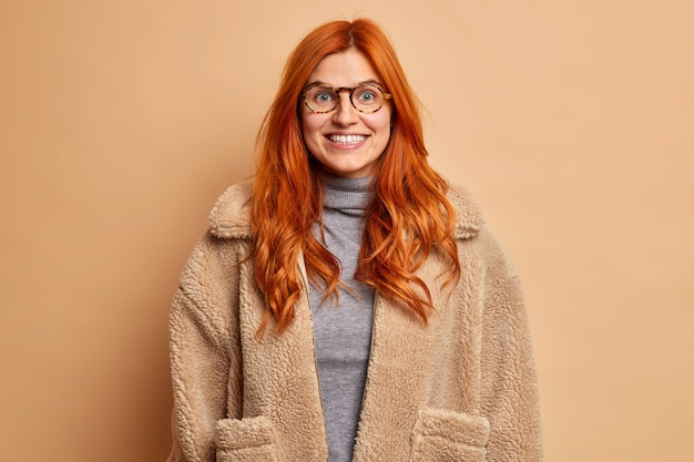 따뜻한 모피 코트를 입은 긍정적 인 빨간 머리 여자는 기분 좋게 기분이 좋으며 행복한 감정을 표현합니다.