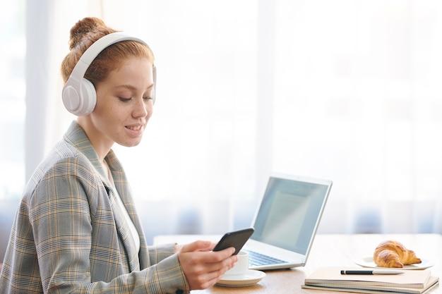 Позитивная рыжая молодая женщина-предприниматель в стильной куртке слушает музыку в наушниках и проверяет телефон при составлении бизнес-плана