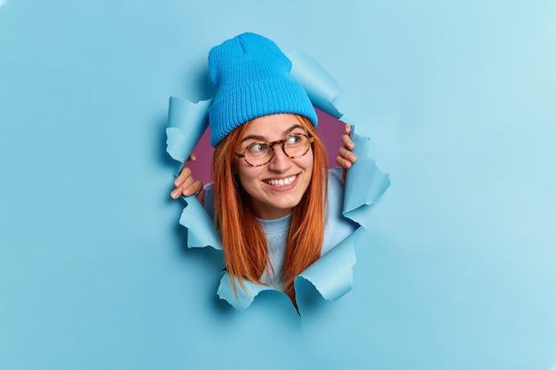 ポジティブな赤毛の若い女性が心地よい笑顔で目をそらし、好奇心旺盛な表情で帽子をかぶり、光学メガネが青い紙を突破