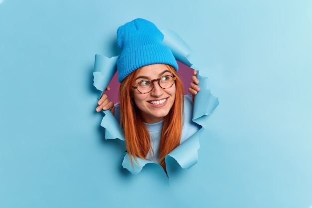 Positive redhead young woman looks away with pleasant smile has curious expression wears hat and optical glasses breaks through blue paper