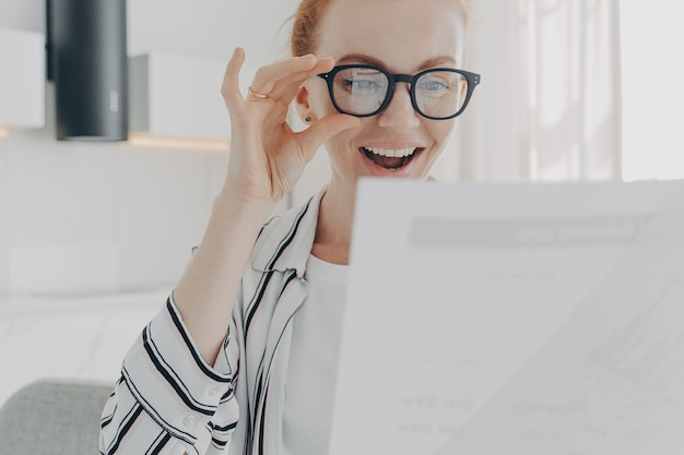 Positive redhead young woman smiles broadly wears transparent glasses focused at papers