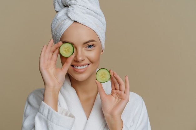 Positive refreshed beautiful woman holds slices of fresh cucumber makes mask for face skin