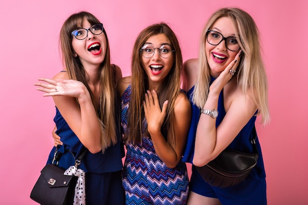 Positive relation friendship concept, three cheerful pretty woman's having fun together hugs and surprised emotions, color matching evening outfits and accessories, cute emoticons, group party time.