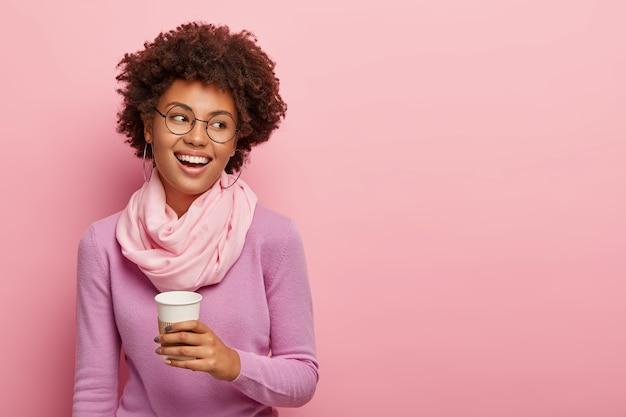 ポジティブなリラックスした巻き毛の女性労働者はコーヒーブレイクを楽しんで、同僚と話をしています