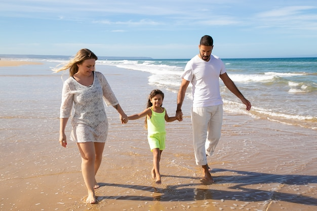 Positive relaxed family couple and little girl walking on wet golden sand on beach, kid holding parents hands