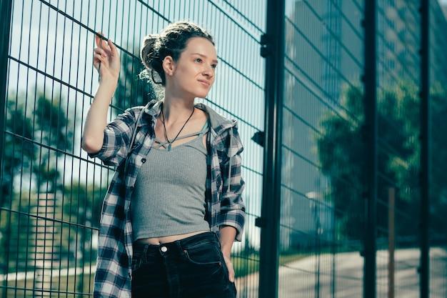 カジュアルな服を着て、金網柵の隣に立っている間、思慮深く遠くを見ているポジティブなリラックスした若い女性